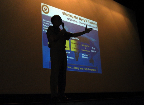 a man giving presentation with slides projected on screen