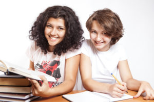 Two college students studying with a pile of books, notebook, and pen.