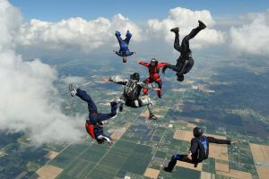 A group of skydivers falling in various body orientations previous to opening parachutes