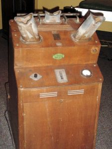 photo of wooden box with dials, switches, and metal parts coming out of it.