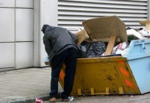 man looking in Dumpster