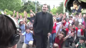 Isaac stepping in front of the crowd of people in the street