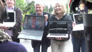 people holding laptop computers with other people on the screens