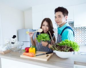 young man and young woman in kitchen making dinner