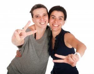 "two girls making ""peace"" signs with their hands"