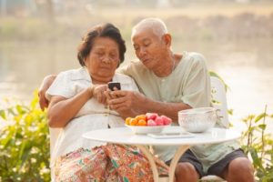 older man and woman sitting at a table outside, using a cell phone