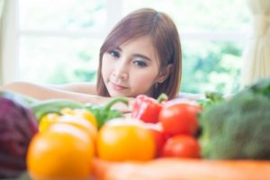 young woman looking at vegetables