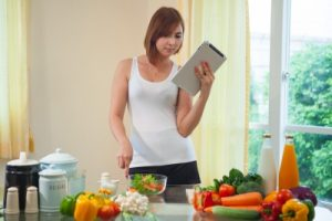 woman preparing food while reading recipe