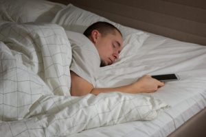 man sleeping in bed with cell phone