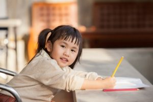young girl with pencil and paper