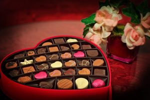 flowers and a heart-shaped box filled with candy