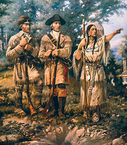 Painting of Lewis, Clark and Sacajawea standing on a hill. Sacajawea has one armed raised and pointing.