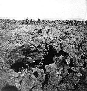Photograph of Kintpuash's Cave, a rocky landscape with a small opening on a rock face. US soldiers stand nearby.