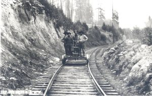 Photograph of maintenance workers traveling down railroad tracks while standing on a handcar.