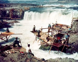 Celilo Falls surrounded by scaffolding. Workers sit and stand on the scaffolding.