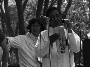 Photo of César Chávez holding a microphone and a folded newspaper