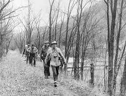 Black and white photo of 5 hikers walking down a tree-lined path