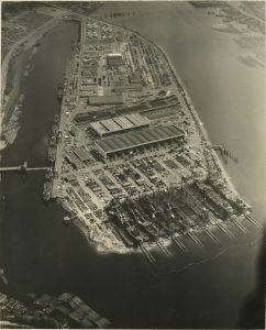 Aerial photograph of Swan Island. On one end of the island, 8 ships are being built