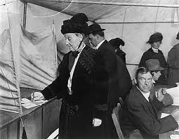 Photo of Abigail Scott Dunniway as she is voting. A man seated behind her turns to watch her
