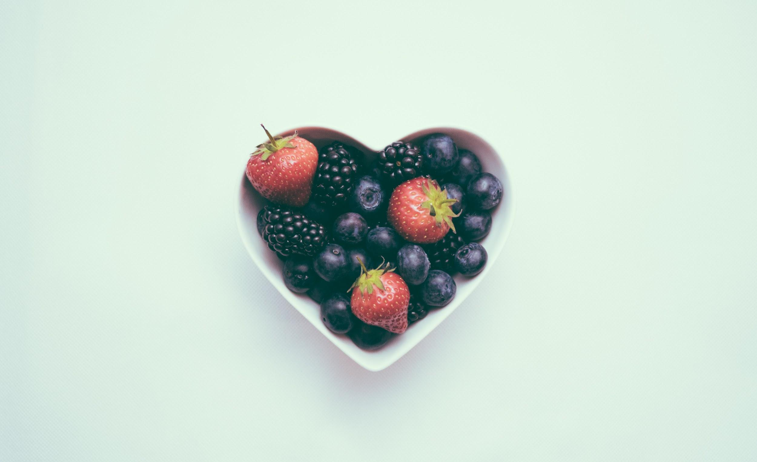 A white heart-shaped bowl filled with blackberries, blueberries, and strawberries
