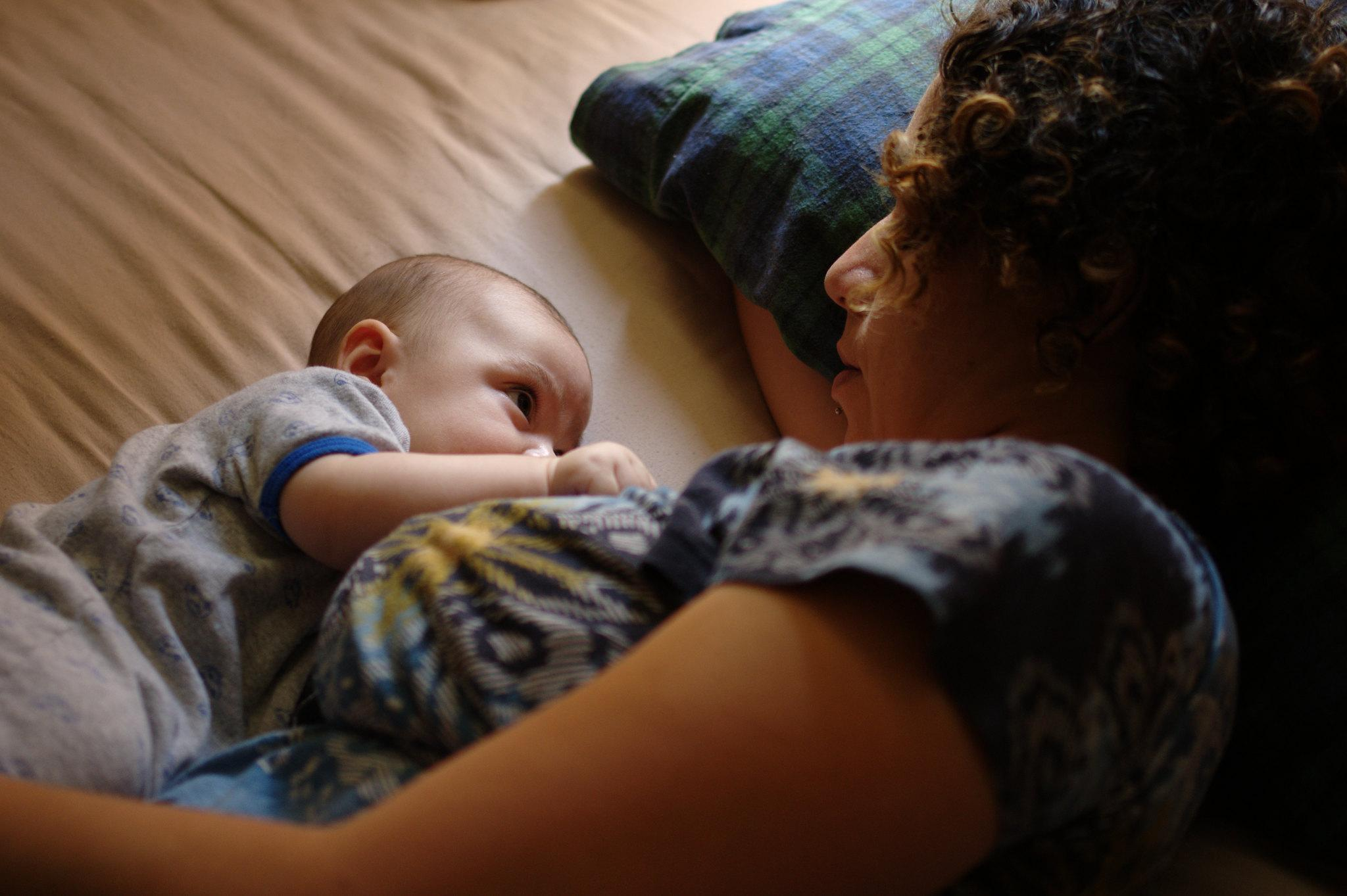 A mother is shown lying comfortably on her side, head propped up by a pillow, with her baby lying next to her and breastfeeding. Mother and baby are making eye contact.