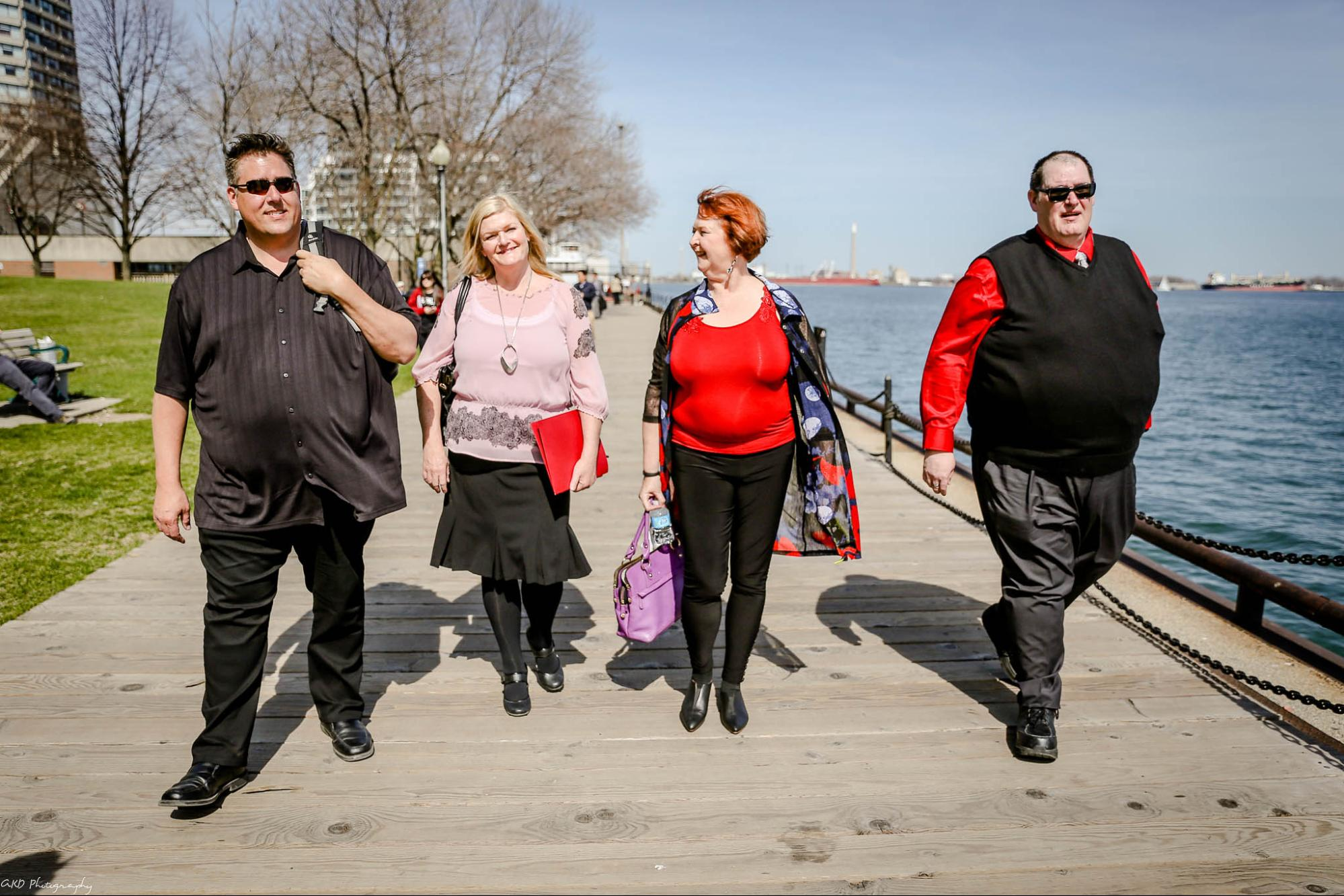 Two adult males and two adult females with obesity are walking outside, smiling and conversing with each other.