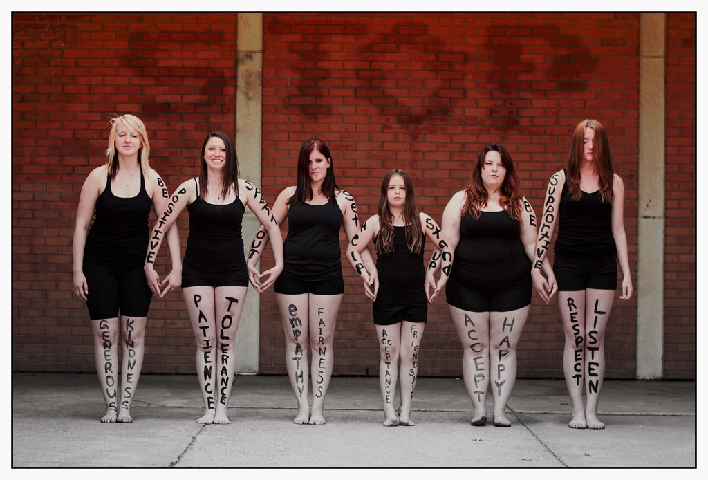 Six young women stand in a row wearing black leotards. The women are of varying body shape and size. They have positive phrases written in large letters on their arms and legs, such as patience, tolerance, be supportive, and be positive.