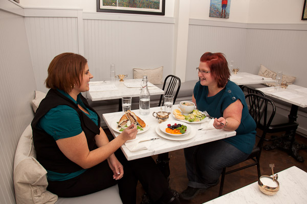 A picture showing two women with obesity eating lunch together. The women are laughing and enjoying their time together.