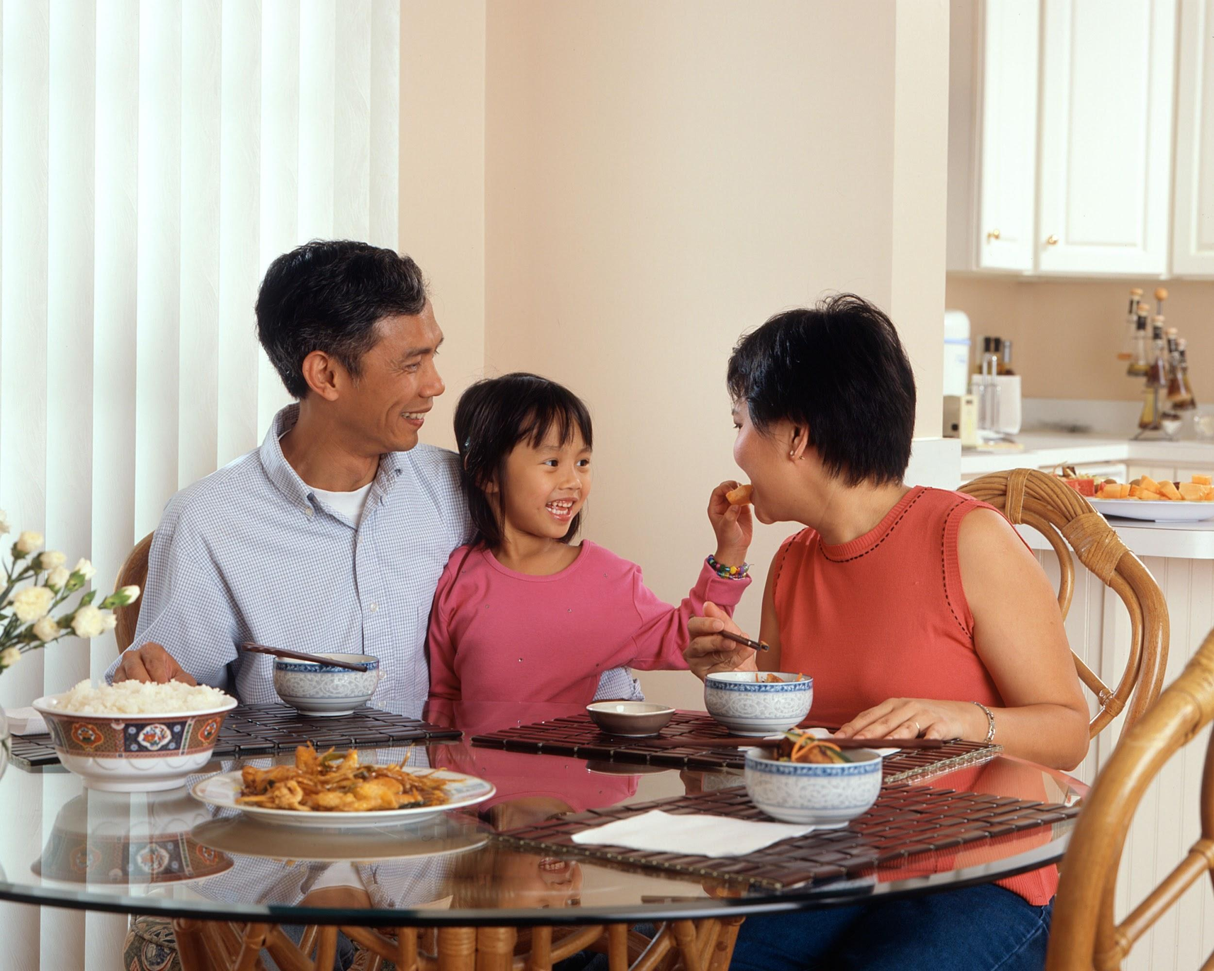 A family of three (mom, dad and daughter) sitting at a glass round table, enjoying a meal of rice and chicken. The young child is feeding the mom a bite of food.