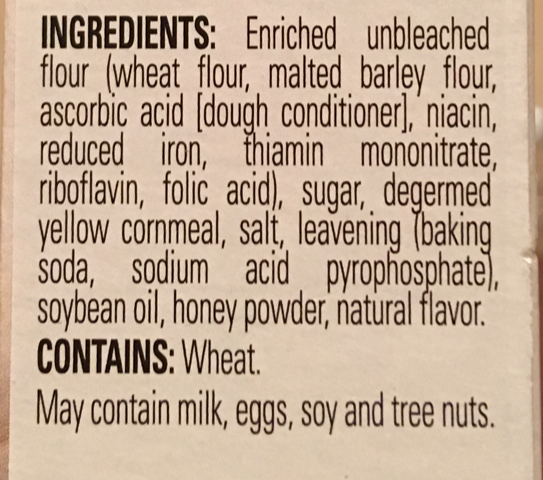 "A photo of the ingredients listed on a cornbread mix. It reads ""INGREDIENTS: Enriched unbleached flour (wheat flour, malted barley flour, ascorbic acid [dough conditioner], niacin, reduced iron, thiamin mononitrate, riboflavin, folic acid), sugar, degermed yellow cornmeal, salt, leavening (baking soda, sodium acid pyrophosphate), soybean oil, honey powder, natural flavor. CONTAINS: Wheat. May contain milk, eggs, soy and tree nuts."