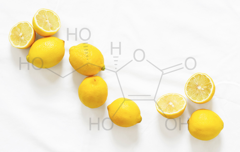 Several lemons are spread out on a white counter top. The chemical structure of vitamin C is shown superimposed over the lemons.