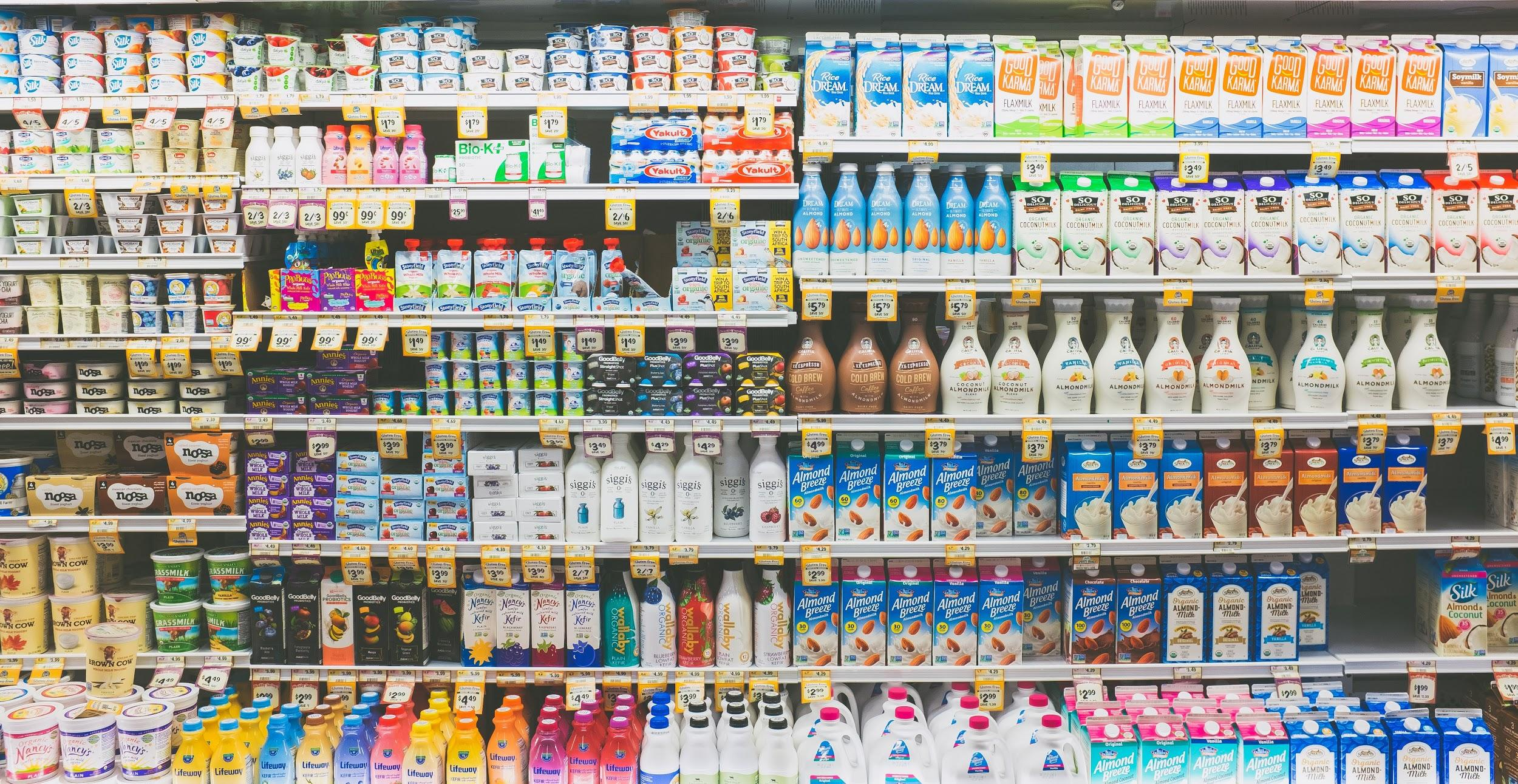 photo of a refrigerated grocery case containing many choices of yogurt, kefir, milk, and plant-based beverage products.