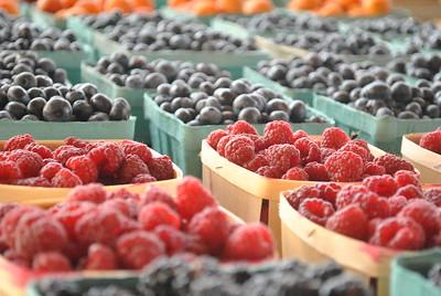 A variety of fresh berries are shown including raspberries and blueberries.