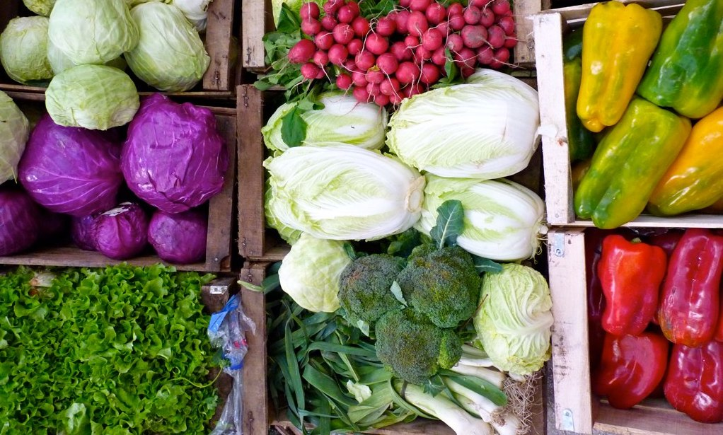 Photo shows a variety of colorful vegetable in bins, perhaps on display at a farmer's market. They include green and purple cabbage, red radishes, broccoli, leeks, lettuce, and red and yellow bell peppers.