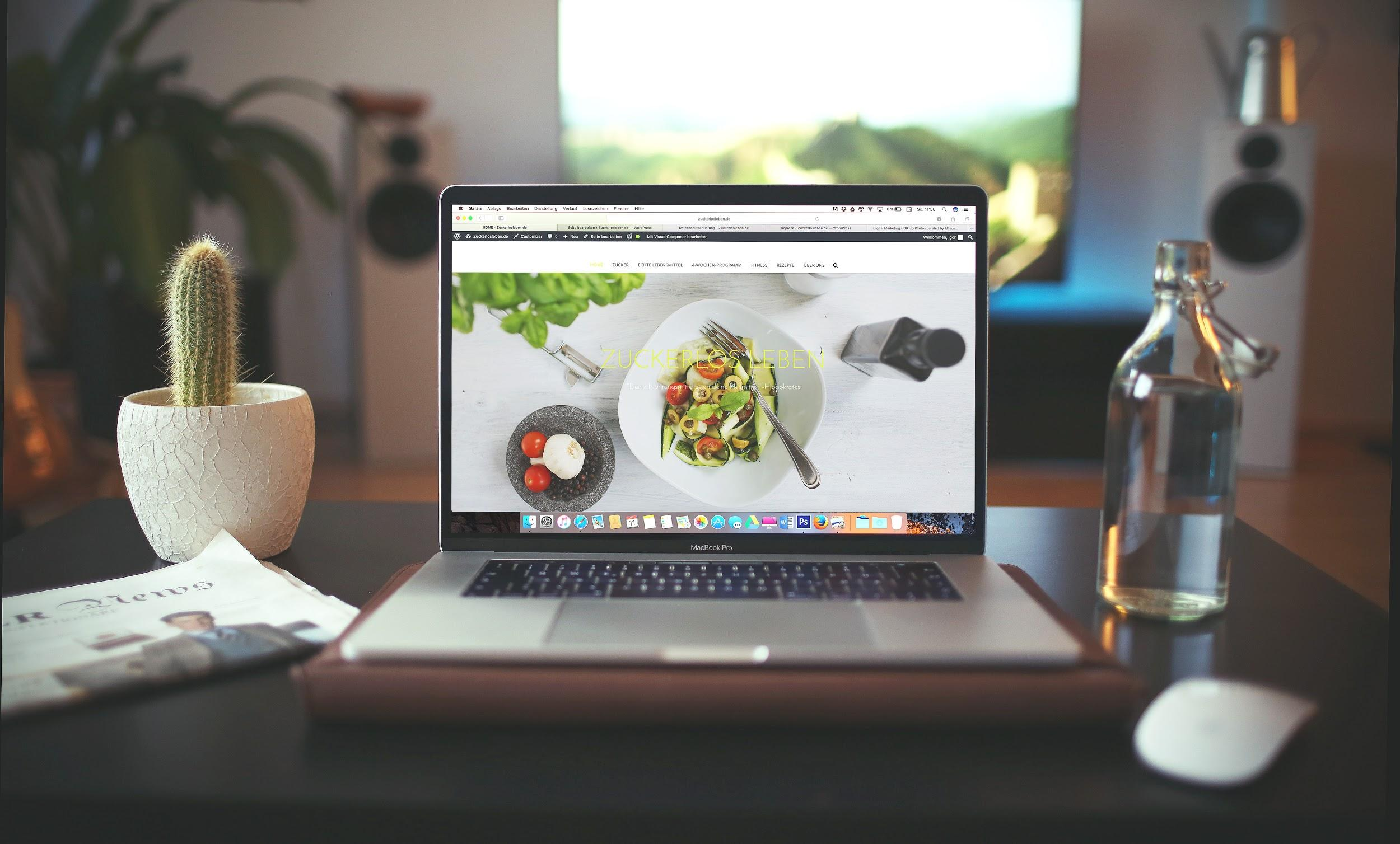 A laptop sits open on a desk showing a website with a bowl of vegetables. The desk also contains a plant, a newspaper, and a glass of water.