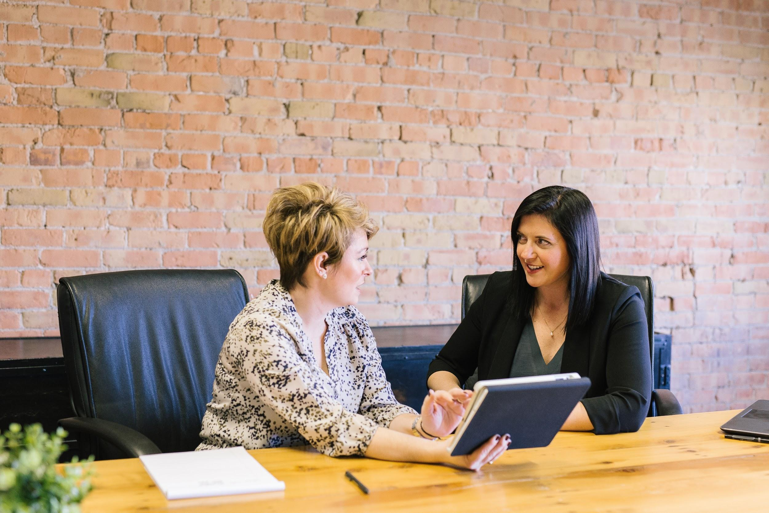 Two women sit at a conference table. One woman is showing some printed materials to the other woman and they are talking together.