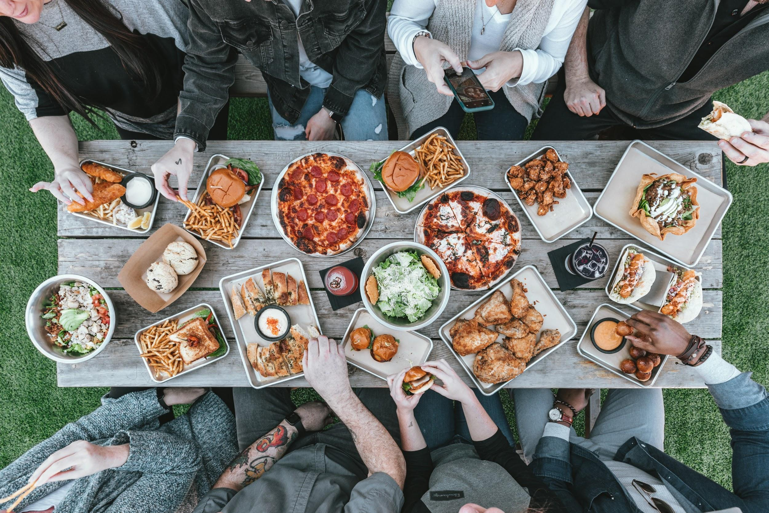 The photo shows a wooden picnic table surrounded by people (just arms and legs showing). On the table are trays holding a variety of foods, including pizza, salads, sandwiches, tacos, and chicken.
