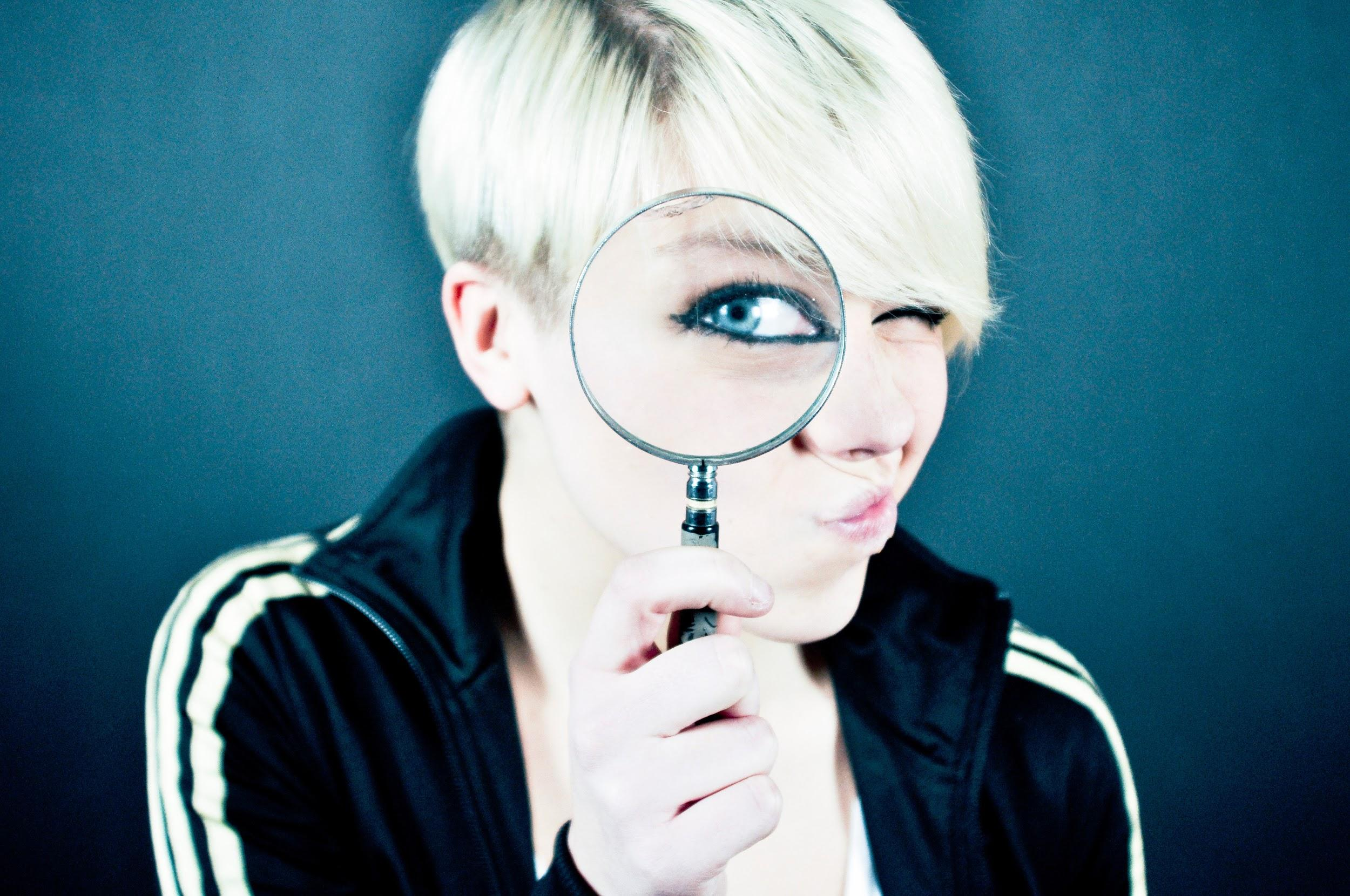 A young woman with short dyed blonde hair and wearing a black and white track jacket peers through a magnifying glass. Through the glass, we can see her blue eye, its edges heavily darkened with eye liner.