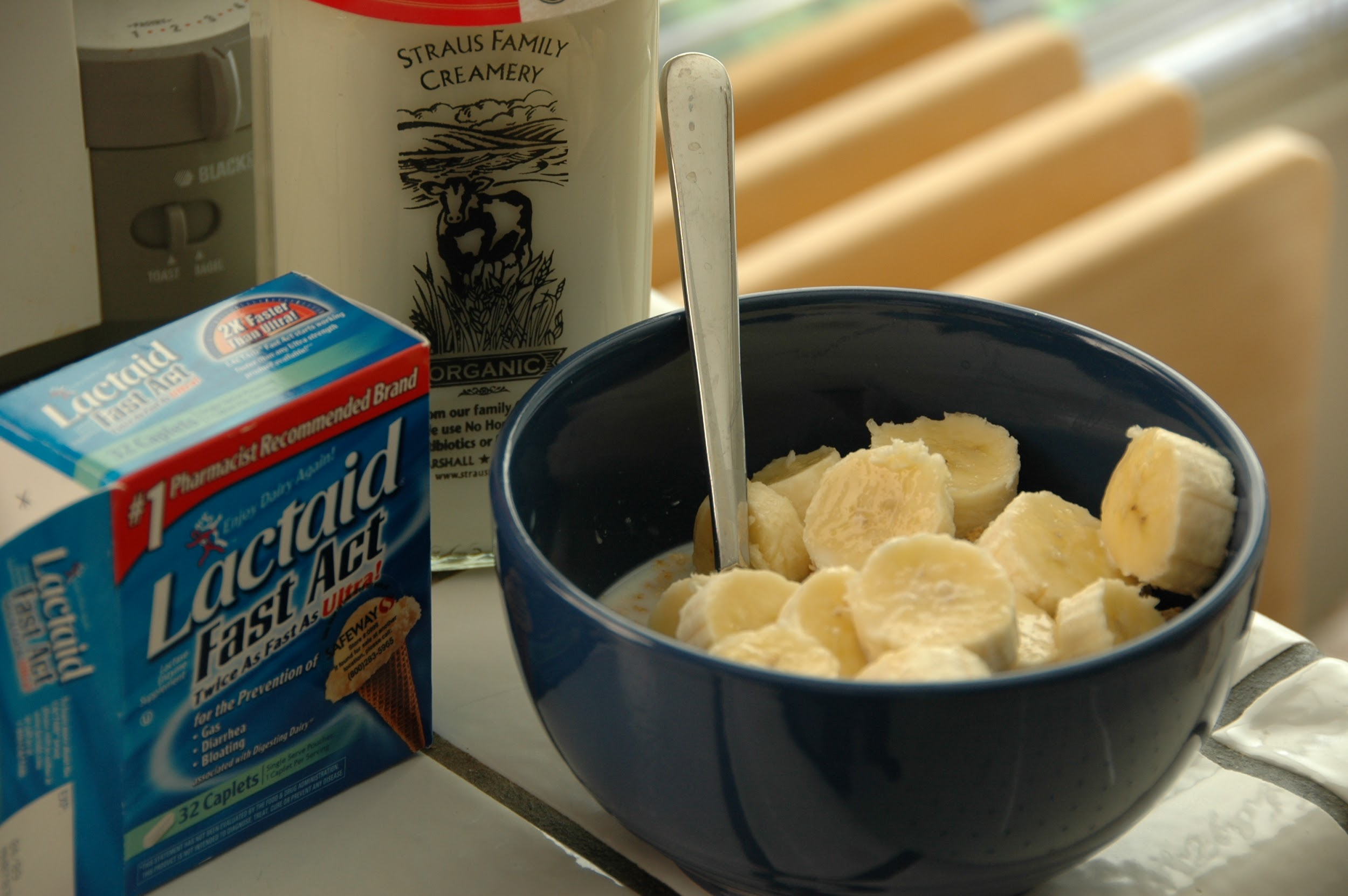 "A photograph depicts a blue bowl of cereal, topped with sliced bananas. Behind it is a glass bottle of milk, and to the left is a box labeled ""Lactaid: Fast Act."""