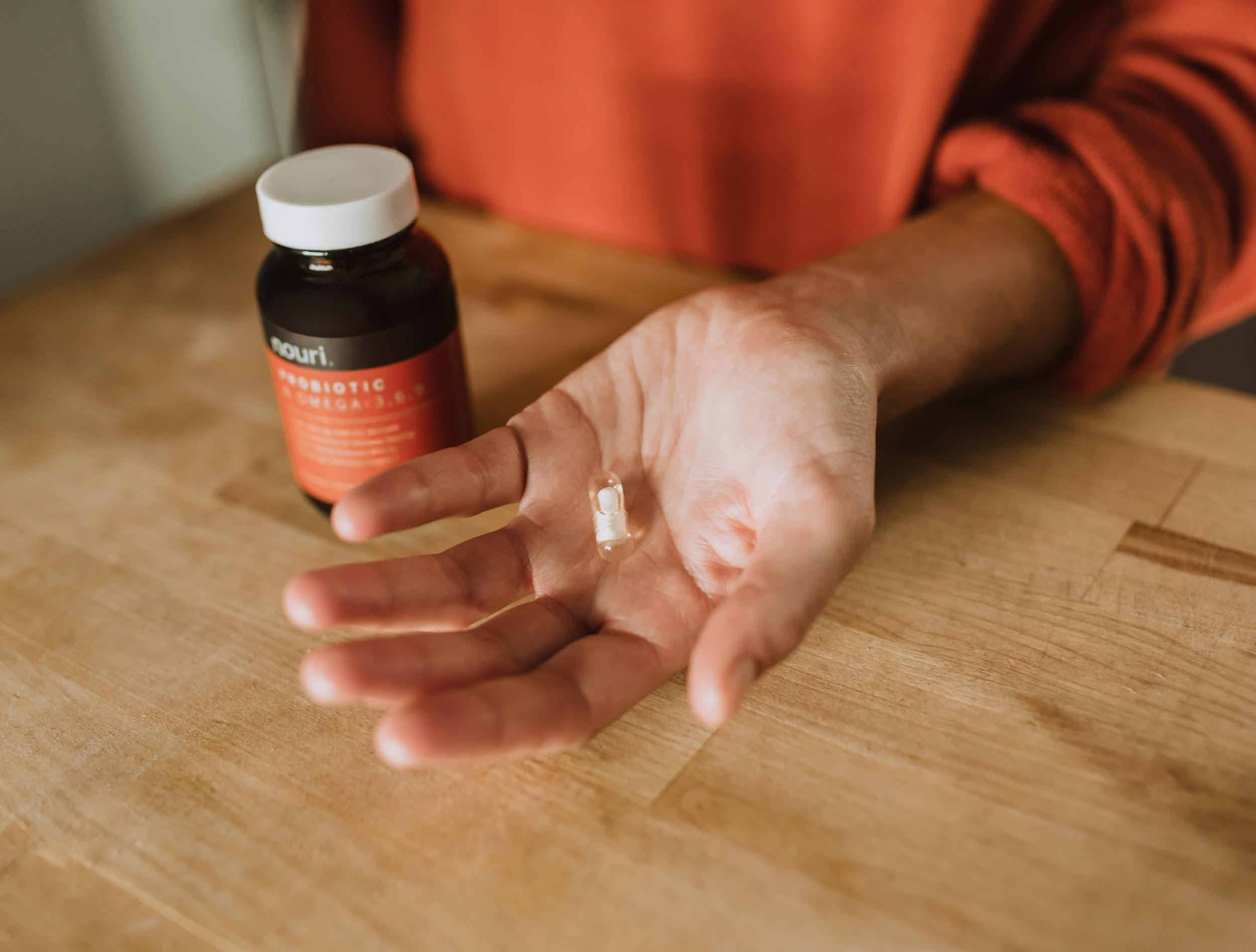 Woman holding probiotic capsule in her hand next to brand bottle over wooden counter.