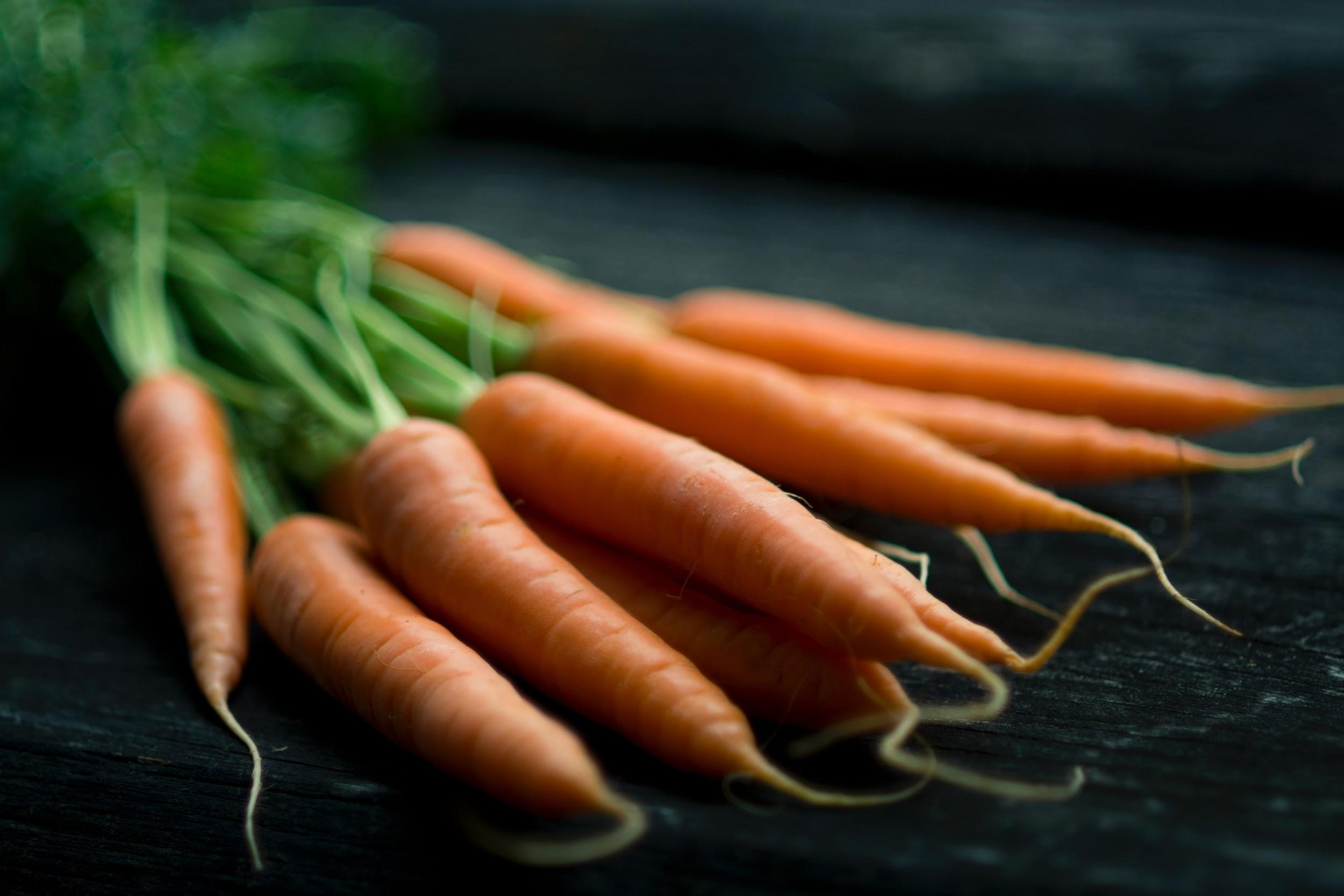 A bunch of orange carrots are shown laying on a dark table