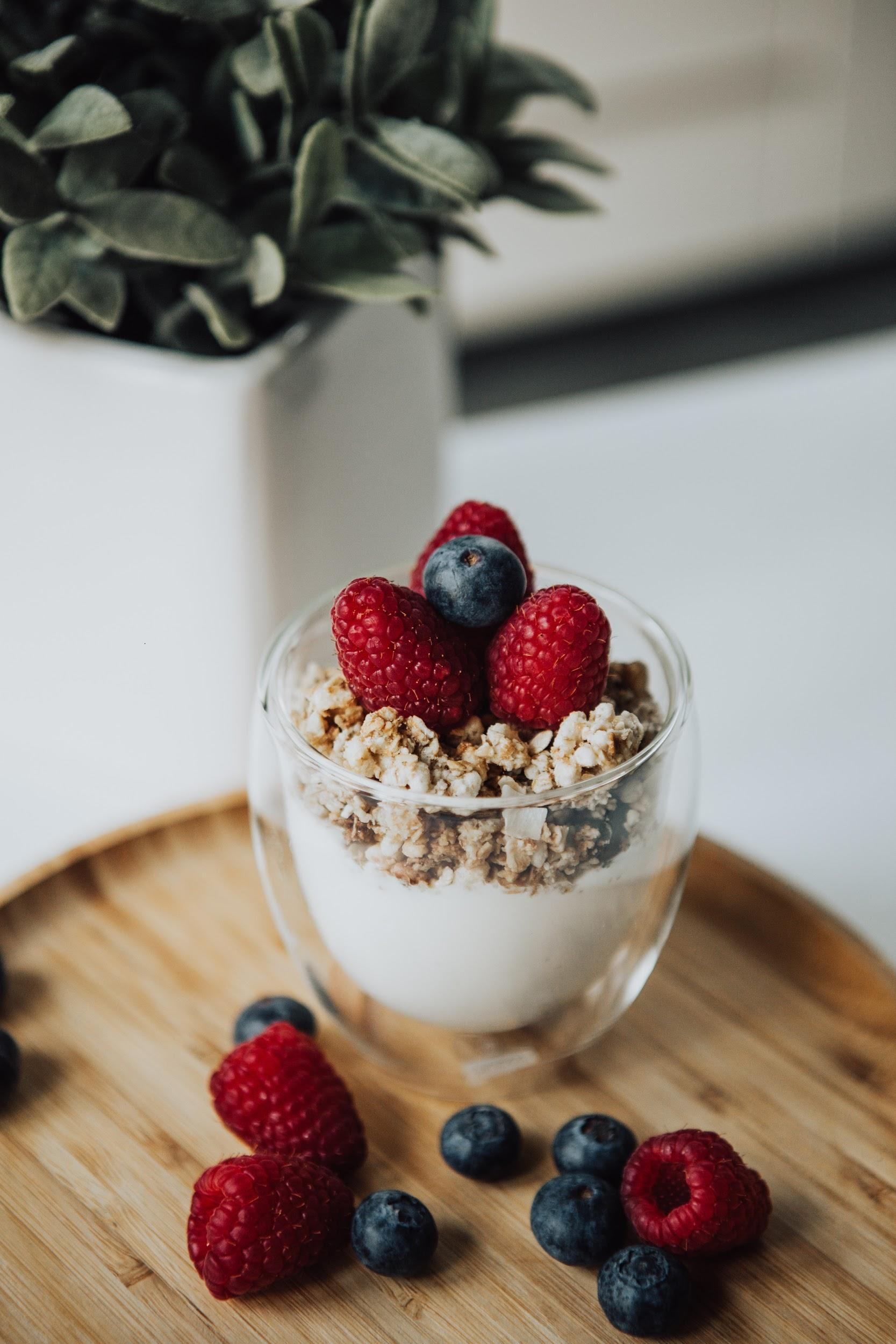 A yogurt parfait with granola and fresh berries in a clear glass is shown sitting on a table