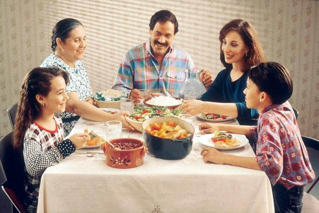 A grandma, mom, dad, son, and daughter all gathered around a family dinner table dishing up food, eating, and smiling.