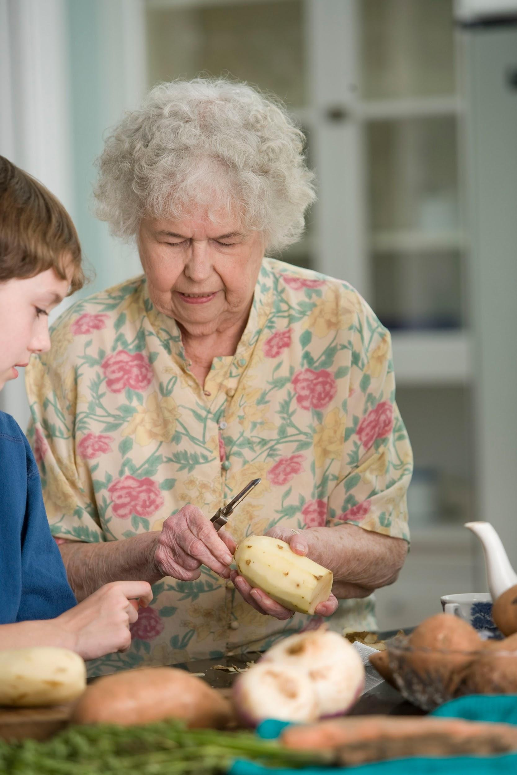 An older woman is peeling potatoes in the kitchen with a male adolescent.