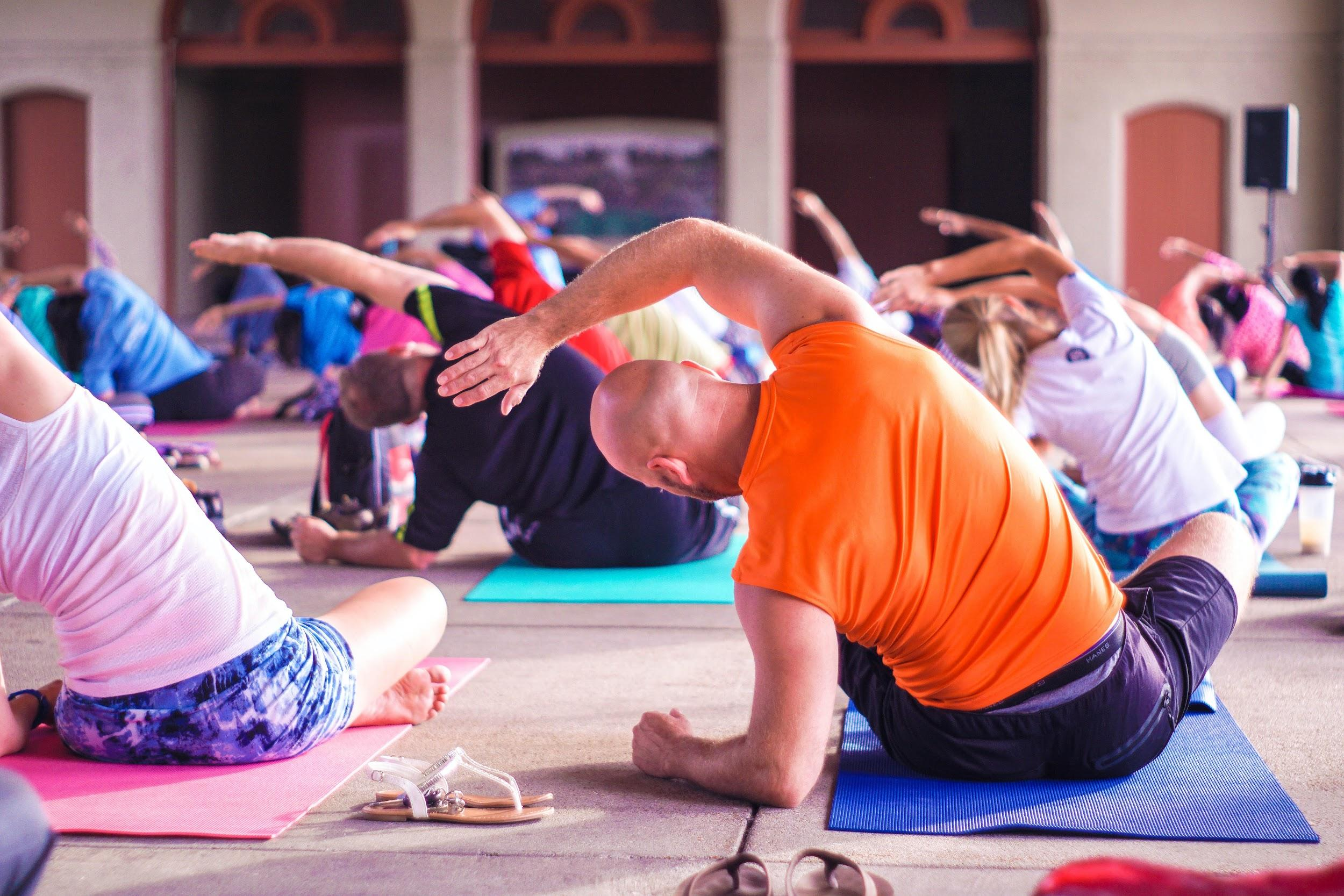 A group of people are shown sitting on yoga mats and participating in a stretching exercise.