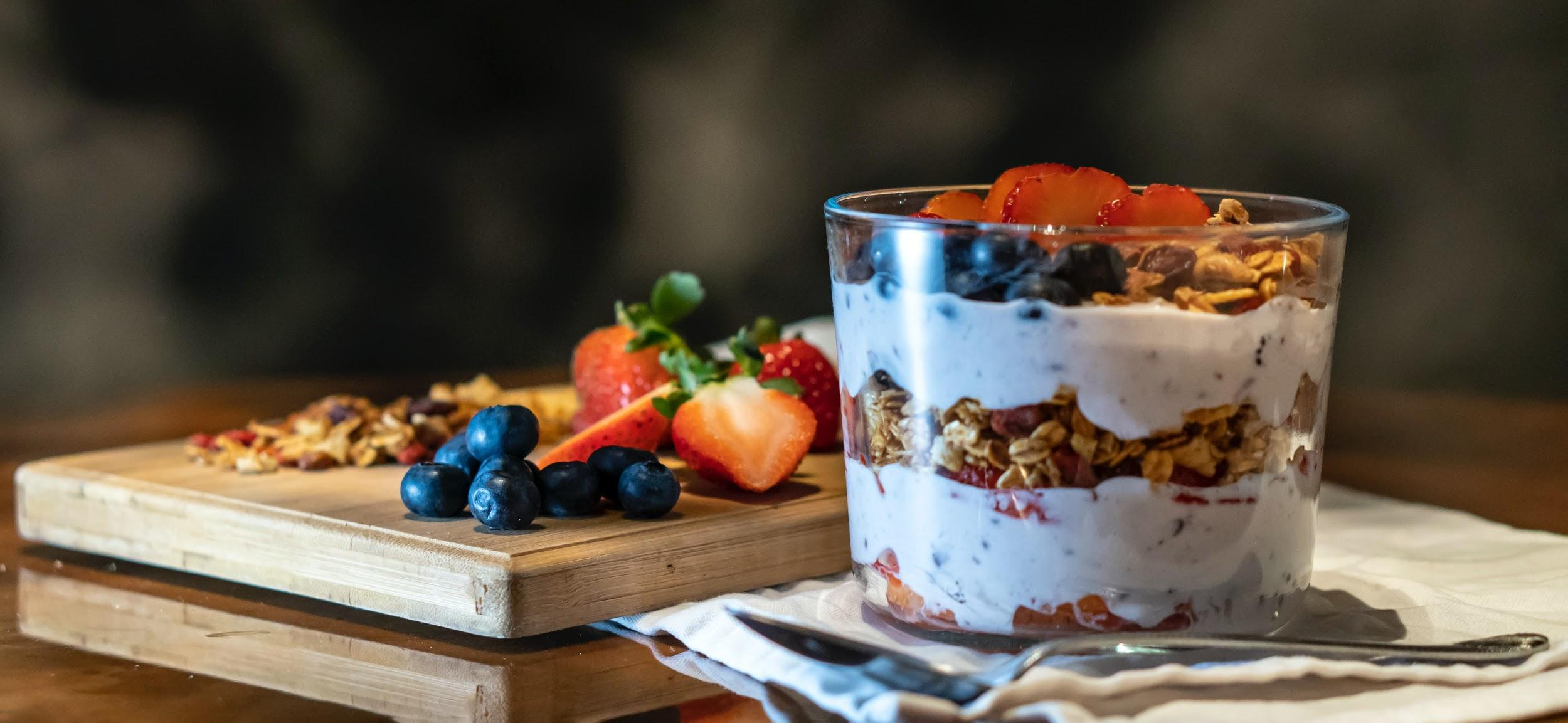 A cup of yogurt with granola and berries
