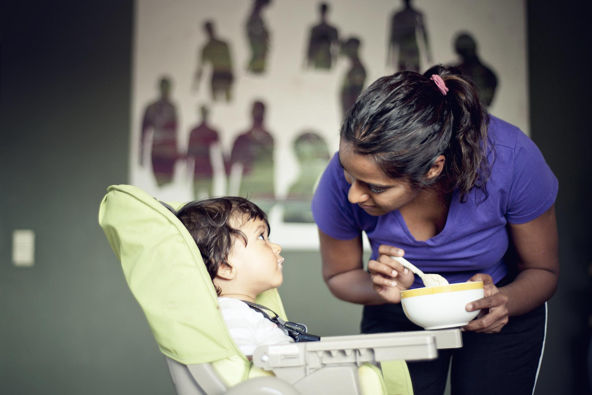 A mother with brown skin tone makes eye contact with a baby in a high chair. The mother is holding a bowl of baby food and a spoon and looks like she's pausing before offering another bite of food to the baby.