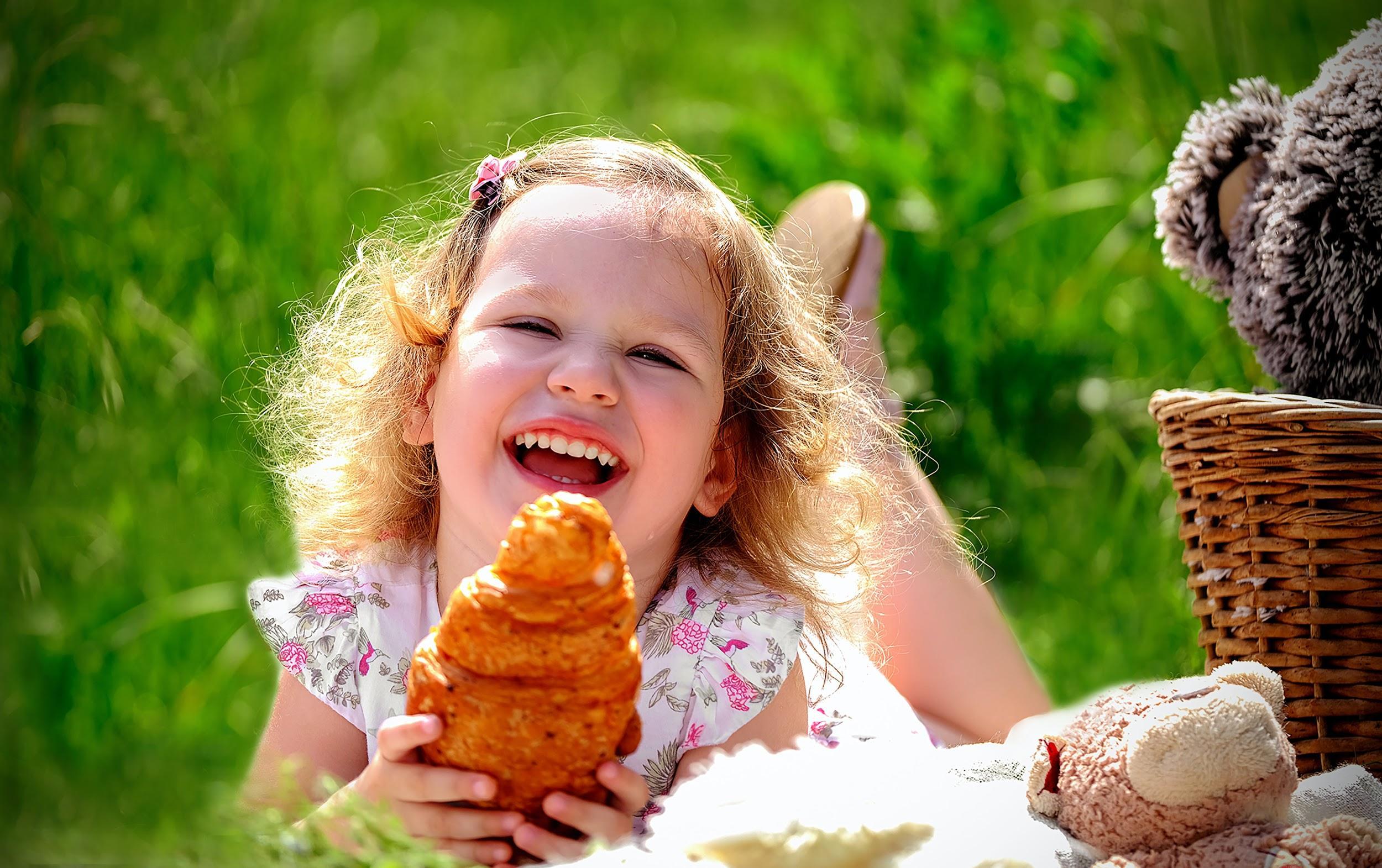 A little girl laying in a field on her tummy. She is looking at the camera smiling and laughing, and holding a croissant.