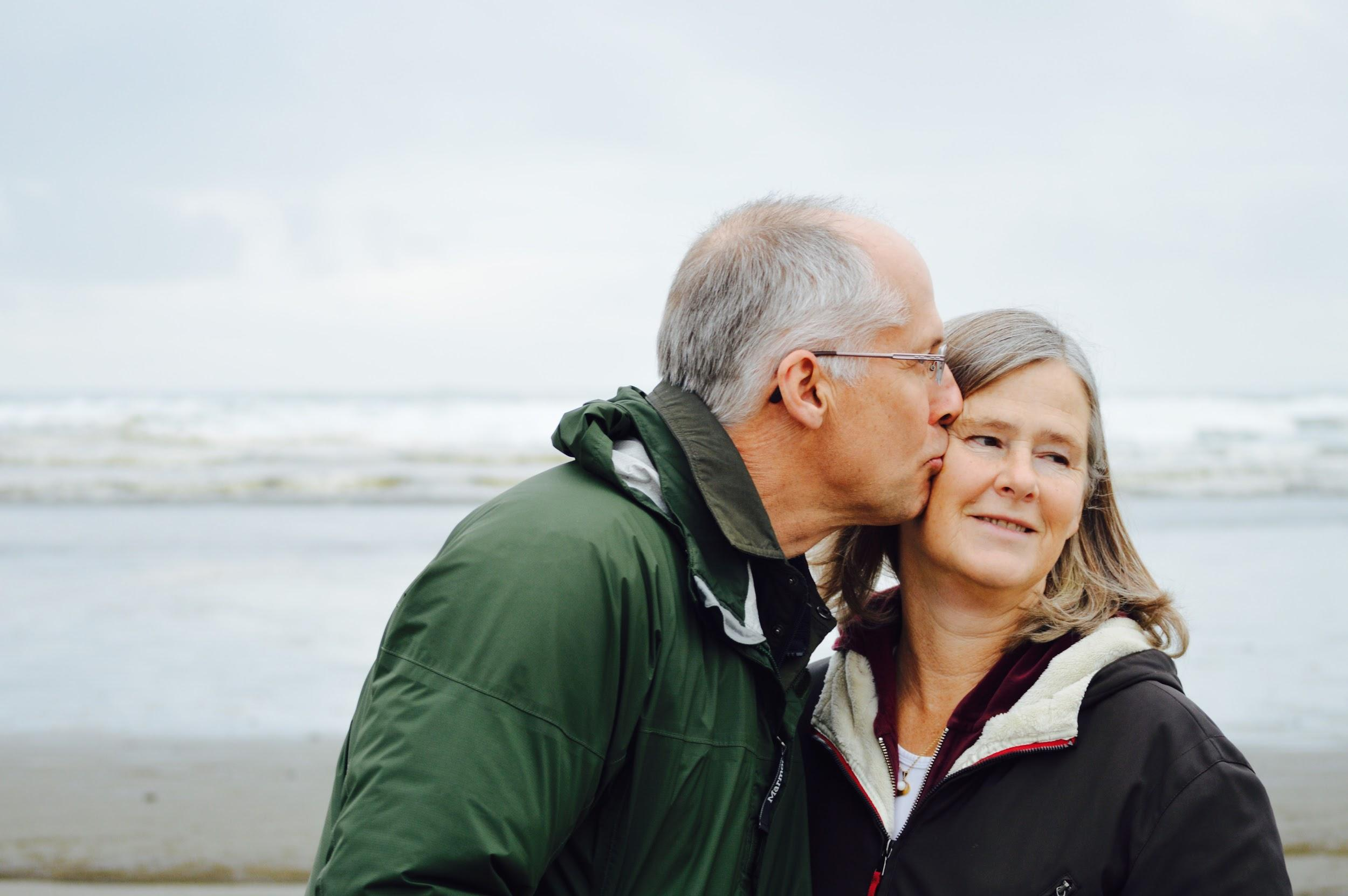 An older male and older female stand on the beach with the ocean behind them. The man is kissing the woman on the cheek.