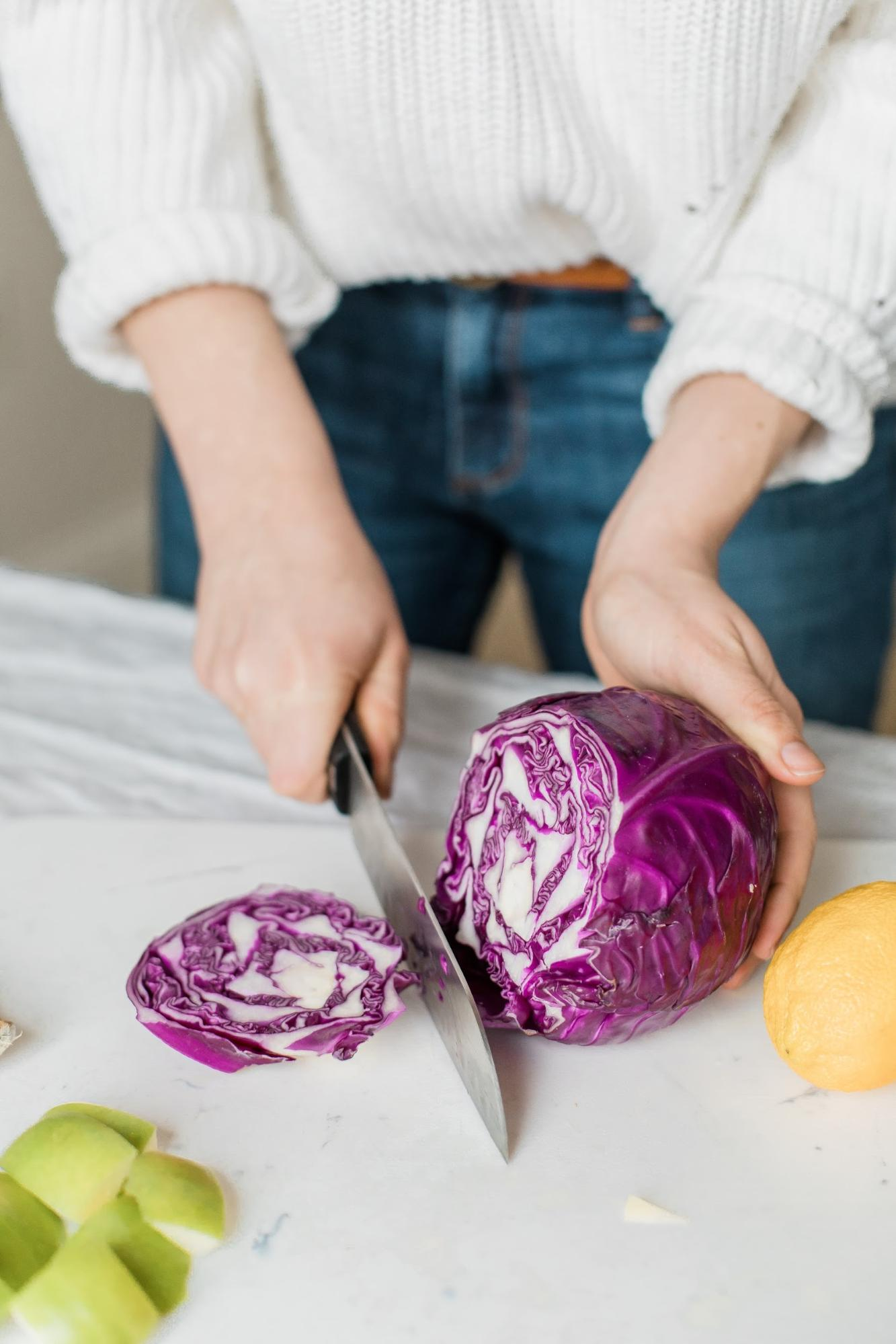 The image shows hands slice a large purple cabbage on a cutting board.
